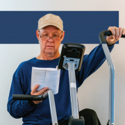 older man on stationary bicycle reading